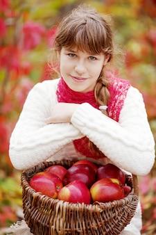 Sorridente ragazza adolescente con cesto di mele nel giardino autunnale. bambino che mangia frutta al raccolto autunnale. divertimento all'aria aperta per i bambini. alimentazione sana