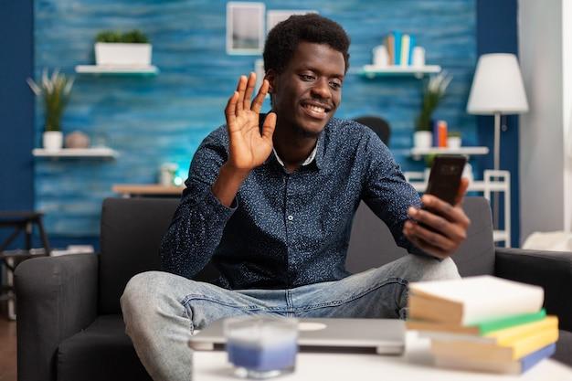 Adolescente sorridente che saluta un collega remoto che discute idee di marketing per il corso universitario durante la riunione di teleconferenza in videochiamata online utilizzando lo smartphone nel soggiorno. telelavoro in conferenza