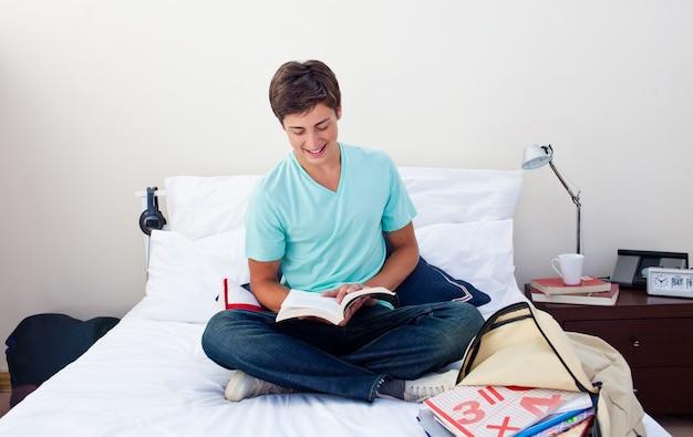 Adolescente sorridente che legge un libro nella sua camera da letto