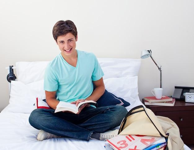Sorridente adolescente studiando matematica nella sua camera da letto