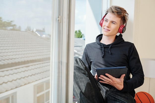 Adolescente sorridente con cuffie e tavoletta digitale seduto sul davanzale della finestra e guardando il cielo quando si resta a casa durante il blocco