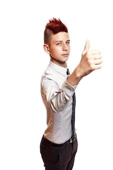 Un adolescente sorridente con camicia e cravatta da portare rosso mohawk mostra il suo pollice in su