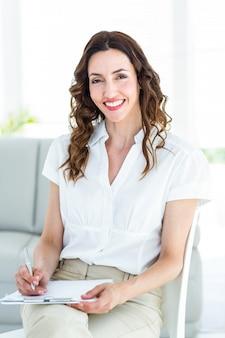 Terapista sorridente prendendo appunti