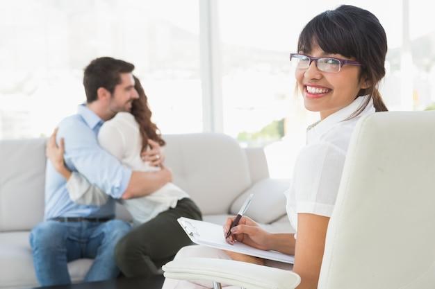 Terapista sorridente con i pazienti che si abbracciano dietro di lei