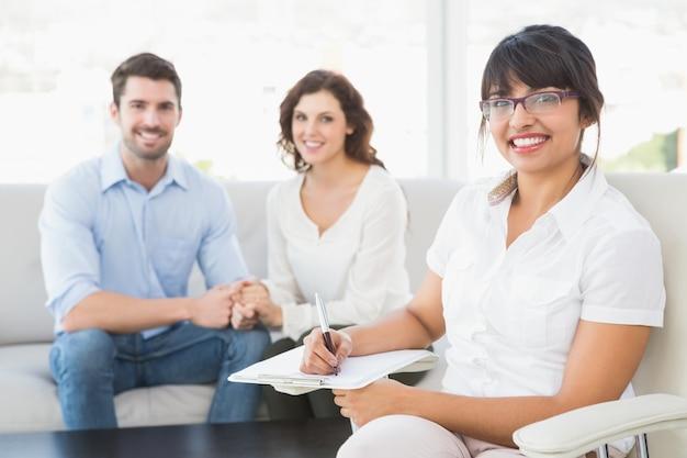 Terapista sorridente con i pazienti che guarda l'obbiettivo