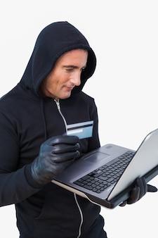 Ladro sorridente in giacca cappuccio usando laptop e carta di credito