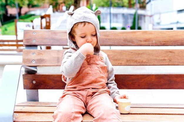 Sorridente bambino di tre anni a mangiare il gelato in strada un giorno d'autunno
