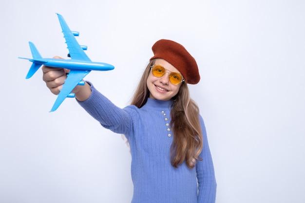 Sorridente testa inclinabile bella bambina con gli occhiali con cappello che tiene fuori l'aeroplano giocattolo