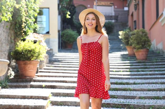 Sorridente ragazza turistica andando al piano di sotto a bellagio, italia. donna giovane viaggiatore durante le sue vacanze estive sul lago di como, europa meridionale.