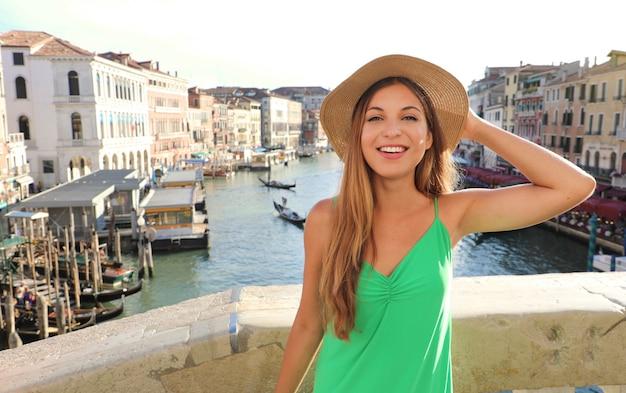 Sorridente ragazza turistica in cappello di paglia a venezia, italia
