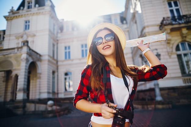 Sorridente ragazza turistica con capelli castani che indossa cappello, occhiali da sole e camicia rossa, tenendo la mappa al vecchio sfondo della città europea e sorridente, viaggiando, ritratto.