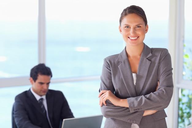 Tradeswoman sorridente con le braccia piegate