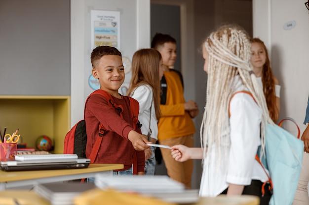 Sorridente due compagni di classe con gli zaini in piedi in classe
