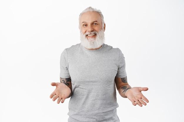 Il vecchio hipster sorridente e rilassato allargò le mani di lato, scrollando le spalle ignaro, sembra disattento e felice, non sa nulla, non ha idea, in piedi sul muro bianco