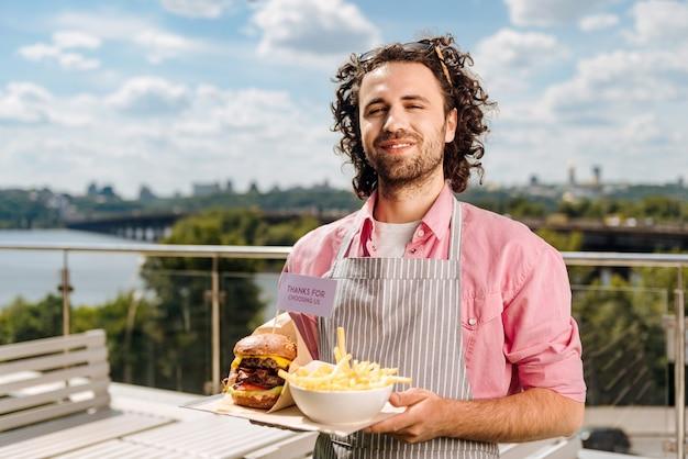 Cameriere sorridente. cordiale cameriere sorridente che si sente eccitato mentre porta l'ordine di fast food per i suoi visitatori