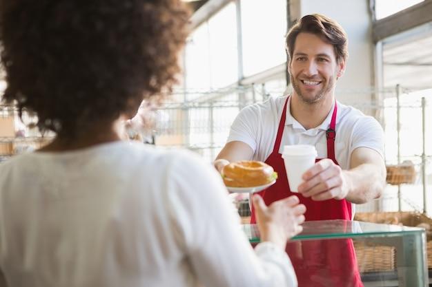 Cameriere sorridente che dà pranzo e bevanda calda al cliente