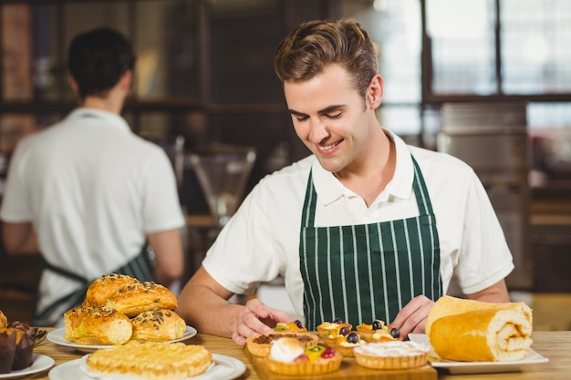 Cameriere sorridente che riordina i pasticcini