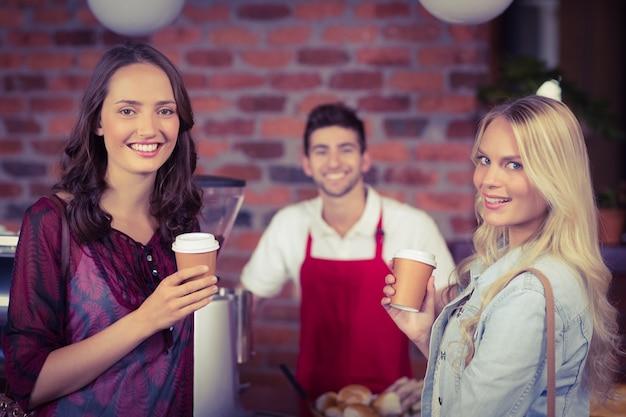 Cameriere sorridente e due clienti guardando la telecamera