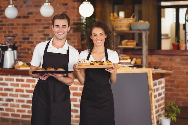 Cameriere sorridente e cameriera tenendo il vassoio con muffin