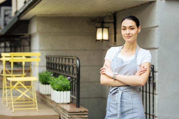 Cameriera sorridente. bella cameriera amichevole che indossa un grembiule e sorride mentre sta all'aperto con le braccia incrociate