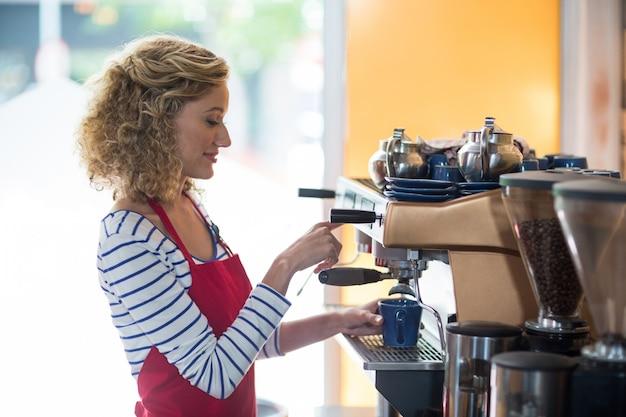 Cameriera di bar sorridente che produce tazza di caffè