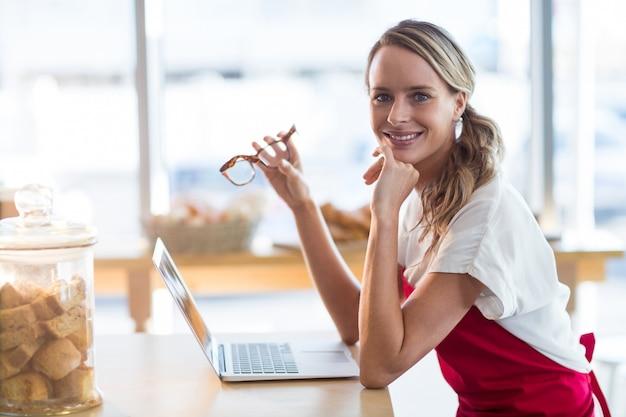 Cameriera di bar sorridente che si siede alla tavola e che utilizza computer portatile nel caffè