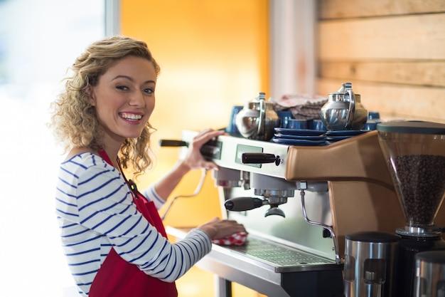 Cameriera di bar sorridente che pulisce la macchina del caffè espresso con il tovagliolo in caffè