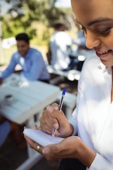 Ordine di scrittura sorridente della cameriera sul blocco note