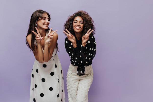 Sorridente donna dai capelli ondulati in camicetta nera e pantaloni leggeri alla moda segni di pace insieme a una giovane ragazza in abito moderno
