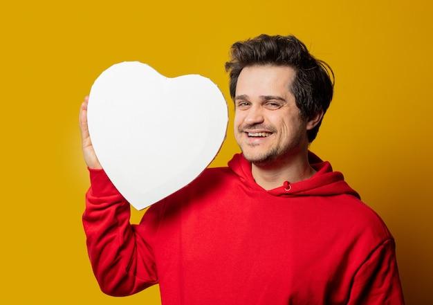 Ragazzo bianco sorridente in felpa rossa con mockup a forma di cuore