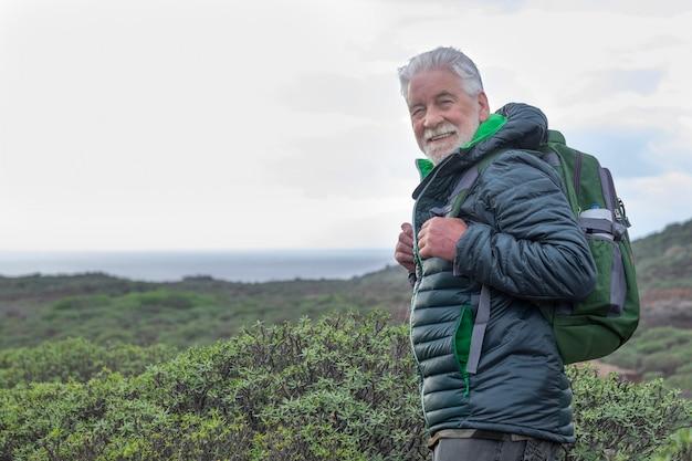 Sorridente uomo anziano dai capelli bianchi che guarda l'obbiettivo mentre fa un'escursione tra i cespugli verdi e il mare. orizzonte sull'acqua. zaino in spalla in pensione attivo che si gode la vita all'aria aperta e la libertà