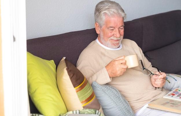 Sorridente uomo anziano dai capelli bianchi si rilassa a casa seduto sul divano con in mano una tazza di caffè e guardando la collezione di un vecchio francobollo. luce intensa dalla finestra.