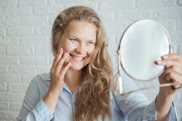 La donna sorridente applica la crema contro le rughe