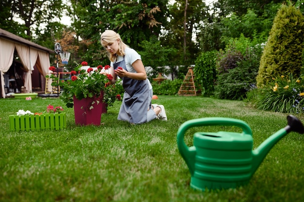 La donna sorridente in grembiule lavora con i fiori nel giardino