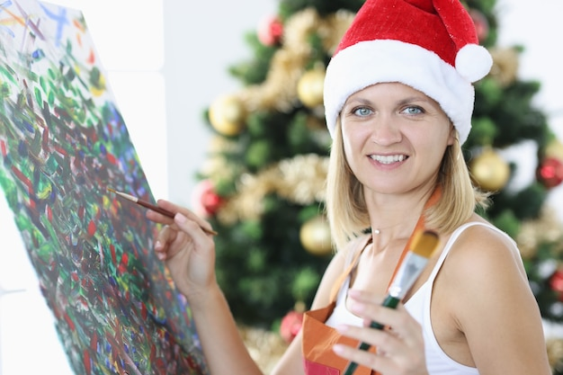 L'artista sorridente della donna in cappello del babbo natale disegna l'immagine contro il fondo dell'albero di natale. artista di professione e concetto di natale