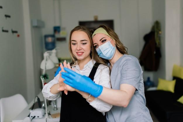 La donna sorridente al salone di bellezza ha una manicure dal maestro di manicure. il maestro sta usando una lima per unghie.