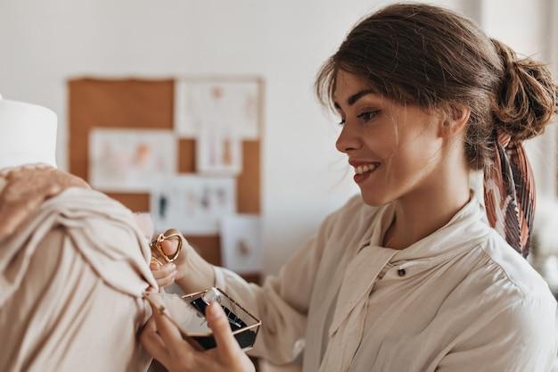 Donna sorridente in camicetta beige che sforbicia in pizzo