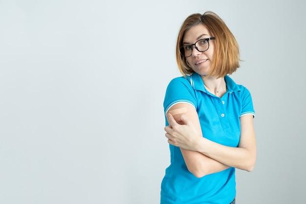 La donna sorridente con una maglietta blu e occhiali con un cerotto sulla mano si rallegra di ricevere una vaccinazione contro l'infezione da coronavirus covid-19 sputnik v