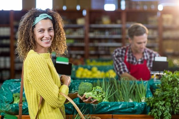 Verdure d'acquisto sorridenti della donna nella sezione organica