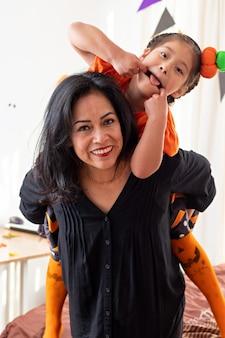 Una donna sorridente che porta una ragazza che guarda la telecamera sotto mentite spoglie di halloween