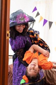 Una donna sorridente che trasporta una ragazza e gioca, sono sotto mentite spoglie di halloween