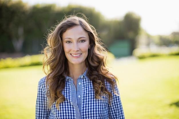 Donna sorridente in camicia a scacchi in piedi in giardino