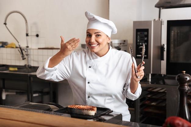 Cuoco unico sorridente della donna che indossa l'uniforme che cucina la bistecca di color salmone delizioso che sta alla cucina