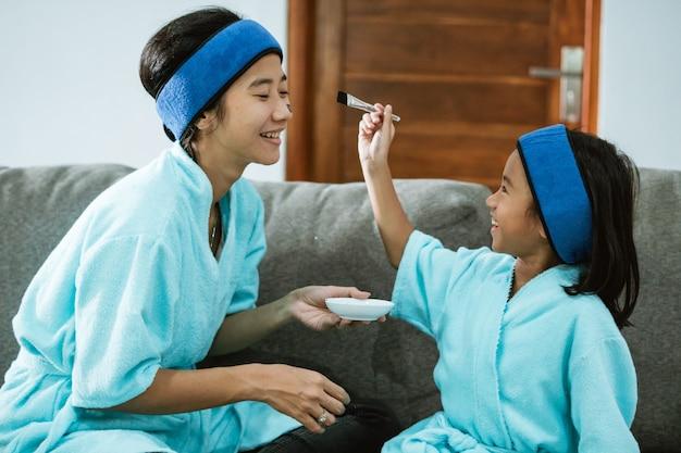 Donna e bambino sorridenti quando si usano maschere facciali di argilla insieme mentre è seduto sul divano