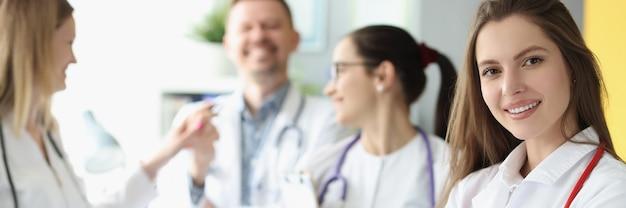 Medico sorridente della donna con lo stetoscopio rosso che sta contro il fondo dei colleghi