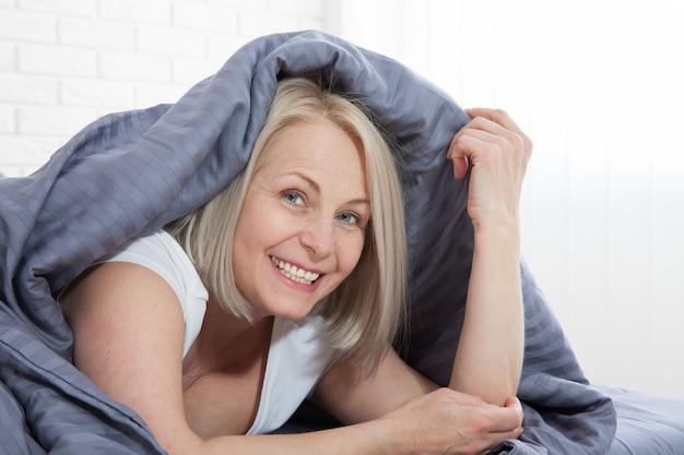 Donna sorridente sotto un piumone nella sua camera da letto. .