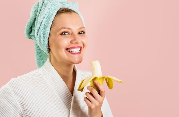 La donna sorridente mangia la banana di mattina.