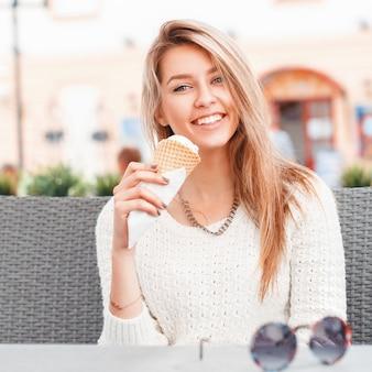 Donna sorridente che mangia un cucchiaio di gelato in un cono di cialda
