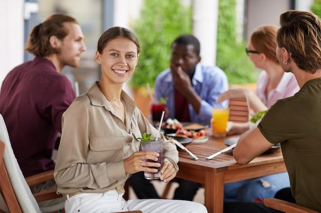 Donna sorridente che gode del pranzo con gli amici in caffè