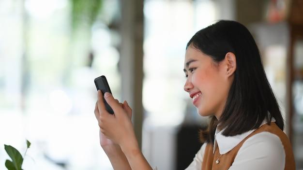 Imprenditore donna sorridente guardando il suo telefono cellulare e sorridente.